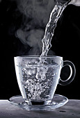 Boiling water being poured into a glass cup