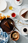Overhead image of tea party with chocolate cheesecake slices on various plates