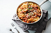 Spaghetti with meatballs, tomato sauce, parsley and cheese served in a pan
