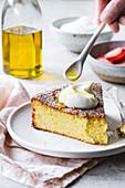 Ein Stück Olivenölkuchen mit Sahne auf Teller