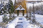 Verschneiter Garten im Winter mit zugefrorenem Teich und Pavillon