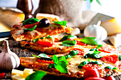 Rustic italian pizza with cheese, tomatoes and basil