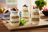 Delicious breakfast served in glass jars with layered yogurt and granola under topping of fresh summer berries