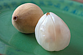 Two langsats, peeled and unpeeled