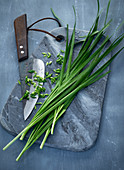 Oriental garlic-chives on a grey marble board with a knife