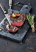 Grilled steak with garlic and a bundle of rosemary on a slate board