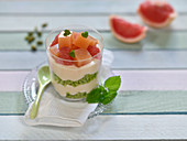 Vegan layered dessert in a glass with matcha and pistachio sponge, soya cream and pink grapefruit