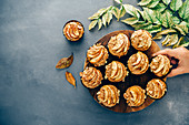 Apple muffins served on a wooden stand on a dark grey backdrop accompanied by fall leaves