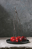 Red caramel apples sweet autumn or Christmas dessert served with branches in black ceramic plate