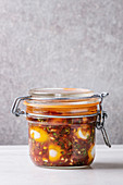 Jar with homemade pickled marinated quail eggs in tomato and olive oil sauce with anchovies and fresh parsley