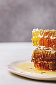 Stack of organic honey in honeycombs in spotted ceramic plate on white marble table
