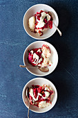 Three bowls of rice pudding with rhubarb and cream
