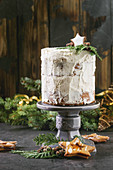 Christmas homemade white naked cake decorated by star cookie and green thuja branches