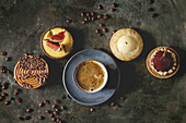 Variety of sweet tartlets with chocolate, caramel, pears, figs with cup of coffee and coffee beans