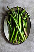Raw asparagus spears on a plate