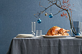 A table laid for Christmas with a roast turkey and a vase with a decorated branch