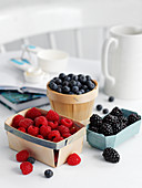 Raspberries, blueberries and blackberries in small bowls