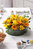 Blumentorte aus Ranunkeln, Osterglocken und Gerbera als Tischdekoration