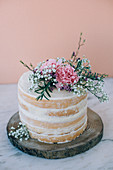A small sponge wedding cake (naked cake) with vanilla buttercream and lemon curd on a wooden slab