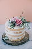 Kleine Biskuit-Hochzeitstorte (Naked Cake) mit Vanille-Buttercreme und Lemon Curd auf Holzscheibe