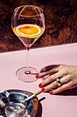 A drink with a blood orange slice, a woman's hand with red fingernails and an ashtray with a cigarette on a bar