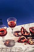 Granatapfel-Wodka-Gimlet mit aufgeschnittenem Granatapfel auf Marmorplatte