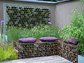 Glasflaschen als Gartenkunst und in Gabionen als Sitzplatz