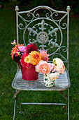 Sträuße mit Dahlien und Rosen auf Stuhl im Garten