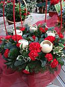 Festliches Gesteck mit Nelken, Stechpalme, Tannenzweigen und Bell Cup als Kerzenhalter
