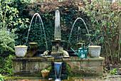 Springbrunnen vor Mauer bewachsen mit Efeu