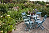Sitzgruppe auf Kiesterrasse im Cottage Garten