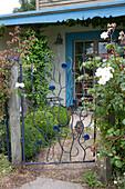 Kunstvoll geschmiedetes Gartentor zwischen Rosen