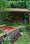Wasserbecken und Gartenhaus