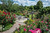 Sitzgruppe auf Terrasse zwischen Rosenbeeten