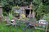 Kleines Gartenhaus im Naturgarten, Fahrrad am Zaun