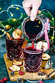 Girl pours Christmas mulled wine with dried apples from a carafe in crystal glasses