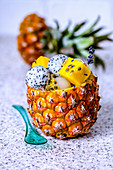 Fruit salad with various tropical fruits in a pineapple with blue transparent spoon
