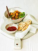 Lammcurry mit Gurkenraita, Butternusskürbis, Naan-Brot und Chutney (Indien)