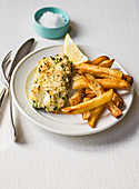 Fish and chips with herb breaded cod and sea salt in blue dish