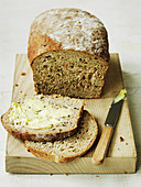 Organic brown bread country loaf with buttered slices
