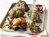 Quail in vine leaves and wrapped in pancetta with red grape compote on a roasting tray