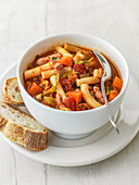 Minestrone soup in bowl with celery, tomatoes, green cabbage pancetta leeks and maccaroni