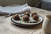 Vegeterian lentil balls garnished with rucola pesto sauce