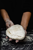 Woman's hands kneading bread on kitchen table