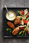 Lentil patties with grilled vegetables and herb sauce