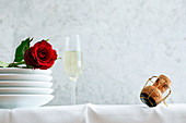 Plates, a rose, sparkling wine, and a champagne cork for the perfect dinner