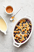 Summer crumble with blueberries and vanilla sauce