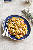 Guinea fowl tortelli in a spicy sauce with pomegranate seeds