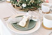 Gedeck mit Kekshäschen als Geschenk auf österlich gedecktem Tisch