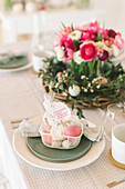 Place setting decorated with Easter basket with flower arrangement in background